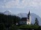 Kostelík (Sv.Duh) v Podolševě. Za ním část hřebene Kamnických a Savinjskich Alp